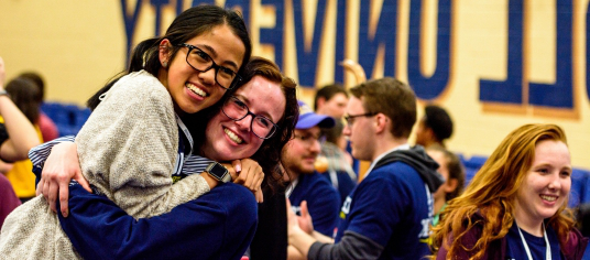 Picture of two current students hugging while volunteering for a campus event with incoming students